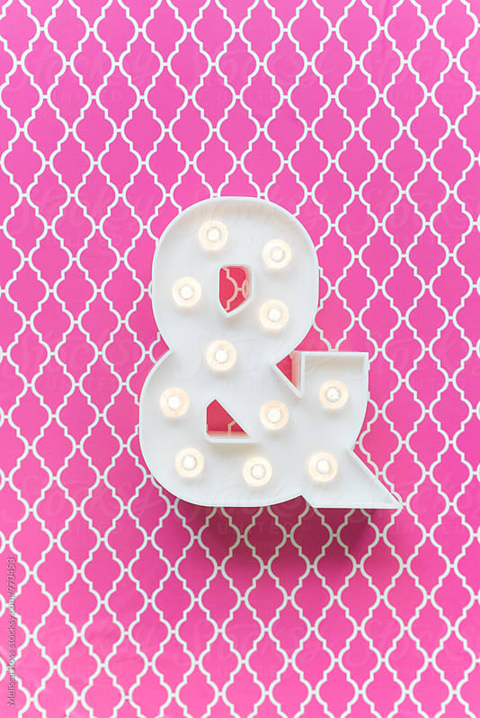 Ampersand marquee light on a pink background by Melissa Ross for Stocksy United