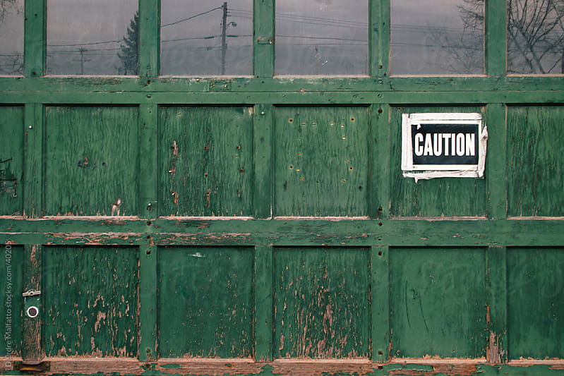 green garage door with caution sign by Deirdre Malfatto for Stocksy United