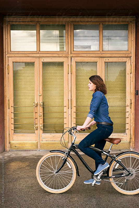 Side view of girl riding bike against of doors by Danil Nevsky for Stocksy United