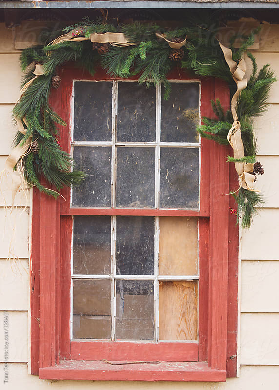 An old window in a shed decorated with evergreen swag for the holiday by Tana Teel for Stocksy United