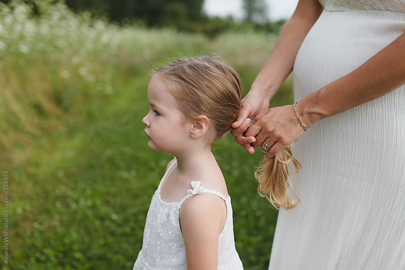 A pregnant mom holds her daughter's hair in a ponytail by Amanda Worrall for Stocksy United