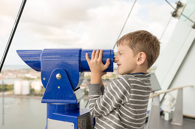 Child looking through a coin operated telescope on an observation deck by Rebecca Spencer for Stocksy United