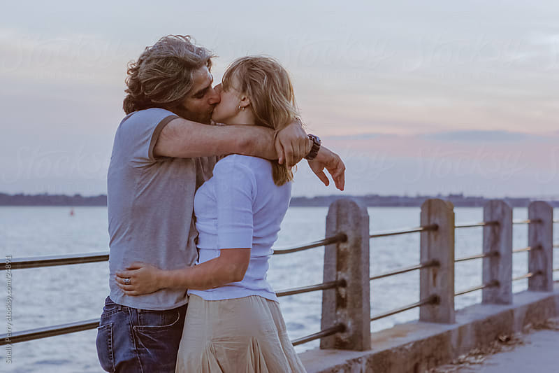 Boardwalk couple at sunset, with a passionate kiss. by Shelly Perry for Stocksy United