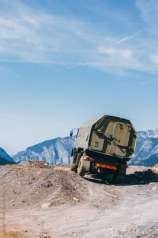 offroad truck in rugged alpine mountain landscape by Leander Nardin for Stocksy United