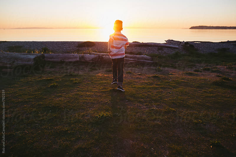 Young boy exploring and running toward sunset by Rob and Julia Campbell for Stocksy United
