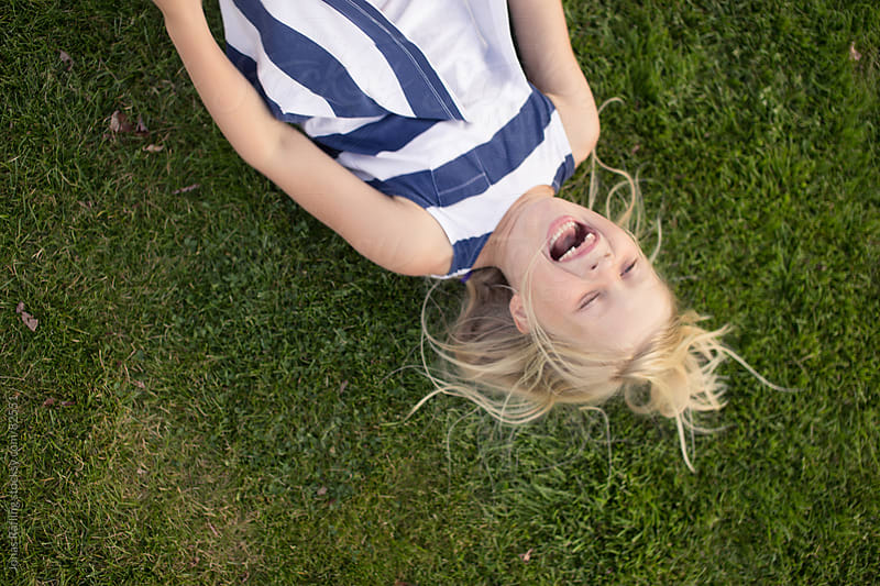 Young girl lying on the grass laughing by Jonas Räfling for Stocksy United