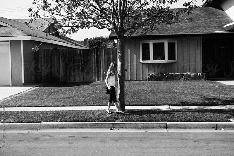 Artistic Image Of Young Girl In Front of Seventies Style House Holding On To Tree by Dina Giangregorio for Stocksy United