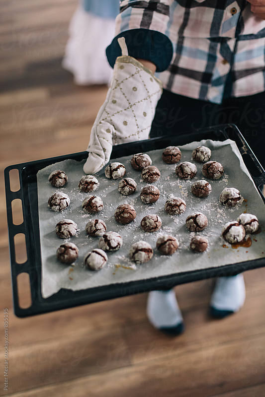 Mother and daughter baking a cakes with Chocolate Crinkles and sweet cakes by Peter Meciar for Stocksy United