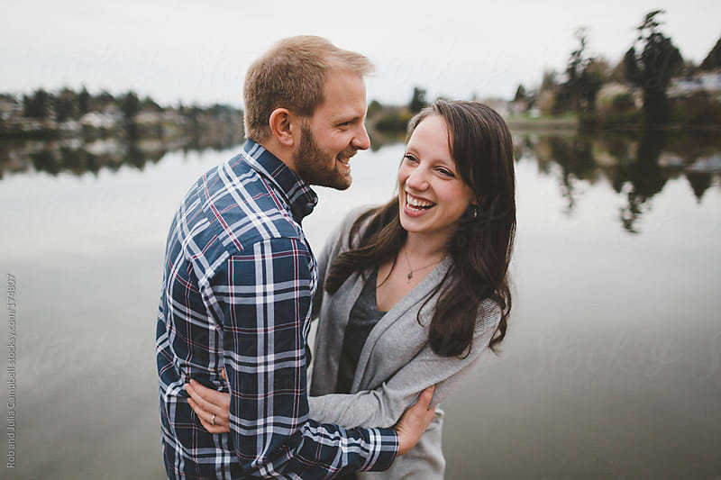 romantic couple - husband and wife - laughing near the water by Rob and Julia Campbell for Stocksy United