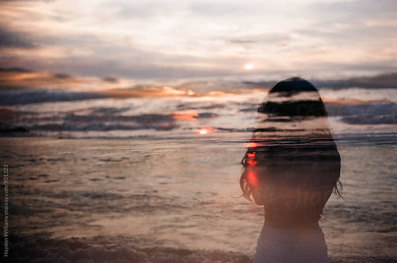 Double exposure of woman staring out into sunset at ocean by Hayden Williams for Stocksy United