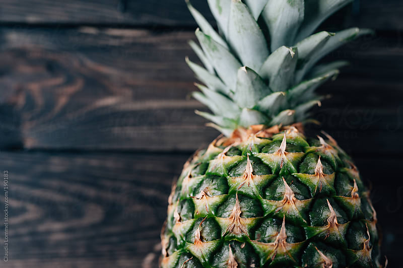 Pineapple on a Dark Wooden Table by Claudia Lommel for Stocksy United
