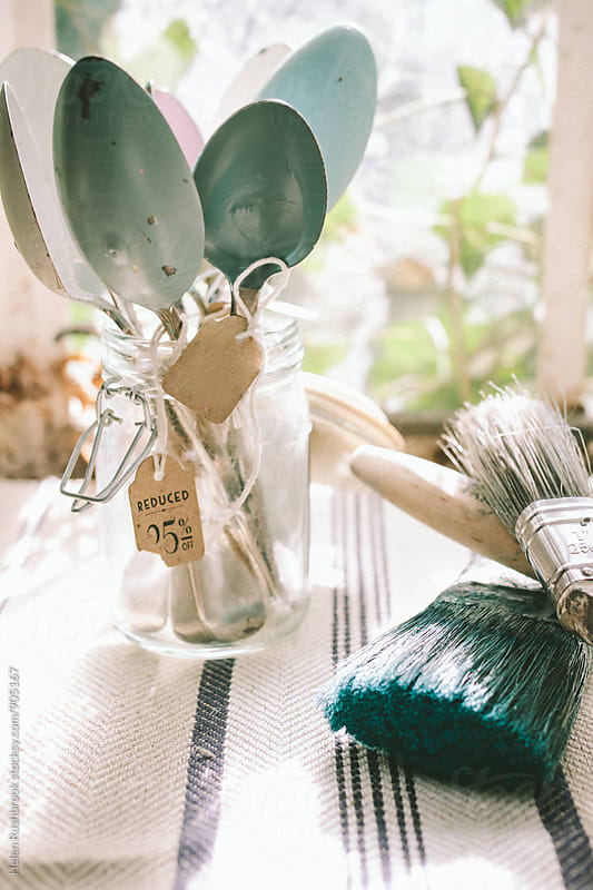 Used paint brushes and a jar with vintage spoons that have paint on them by Helen Rushbrook for Stocksy United
