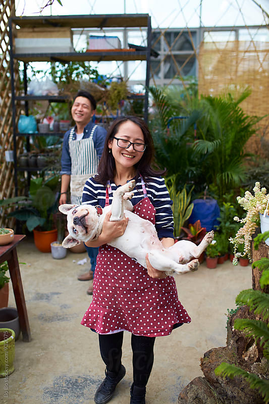 young female florist holding her dog in the shop by Bo Bo for Stocksy United
