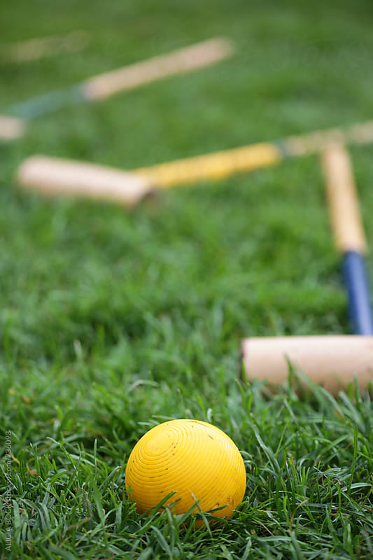 A Yellow Croquet Ball With Vintage Mallets In A Green Lawn Ready For Play by ALICIA BOCK for Stocksy United