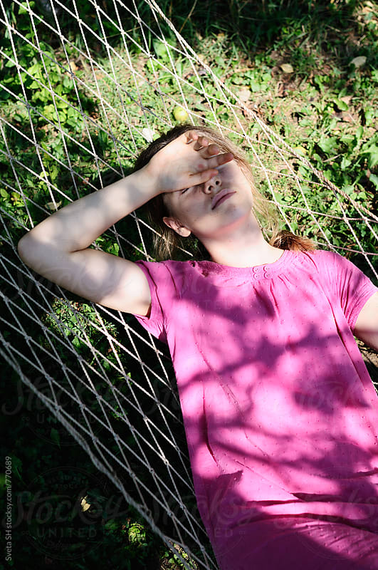 Girl in a pink dress lying on the hammock by Svetlana Shchemeleva for Stocksy United