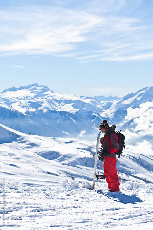 Snowboarder preparing  for riding with the snowy mountains at the background by Ivo de Bruijn for Stocksy United