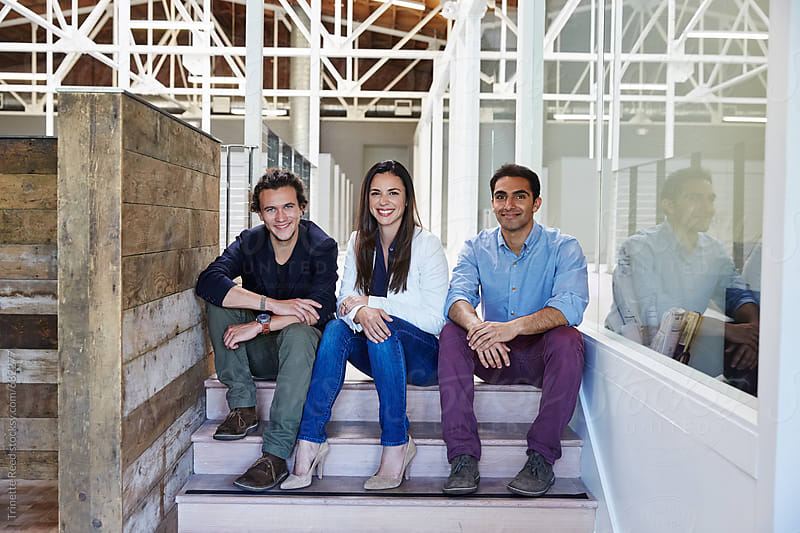 Portrait of millennial business people sitting on stairs  by Trinette Reed for Stocksy United