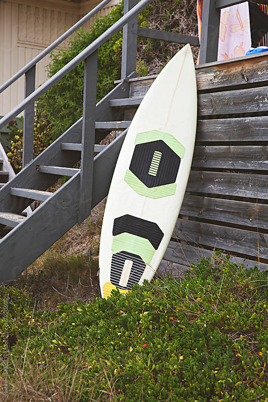 Surfboard leaning up against a bathing box at Portsea Beach by Natalie JEFFCOTT for Stocksy United