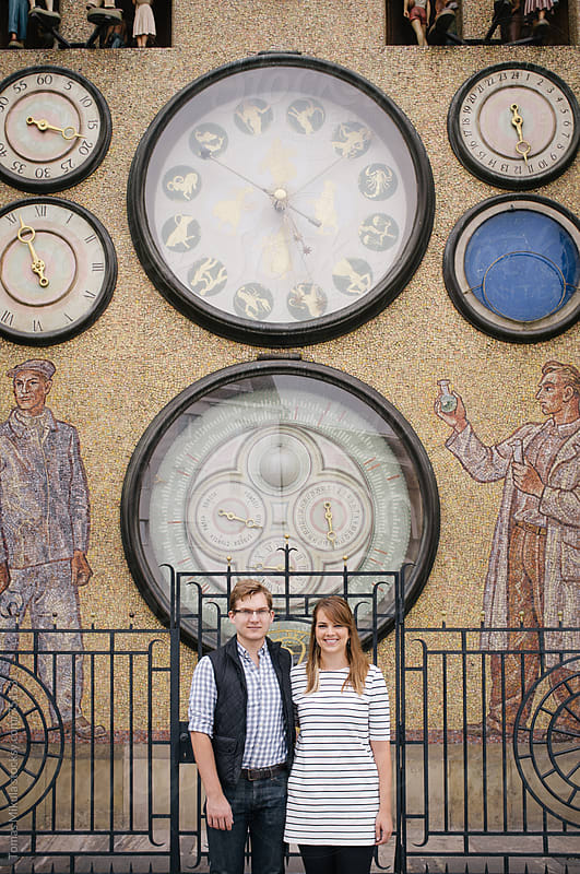 Couple in front of astronomical clock by Tomas Mikula for Stocksy United