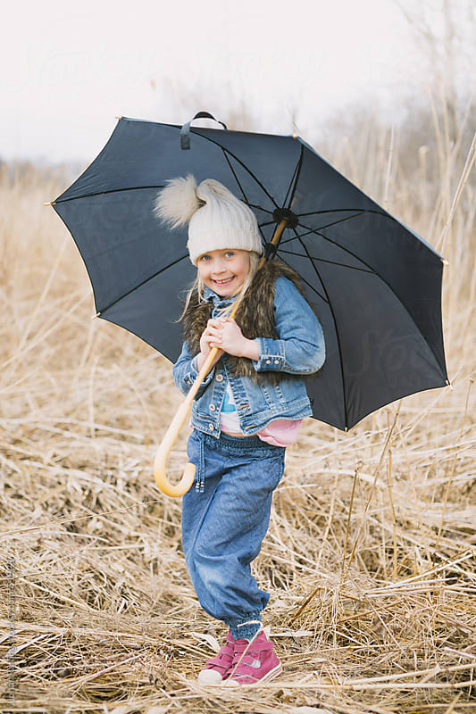 Girl holding a umbrella by Jonas Räfling for Stocksy United