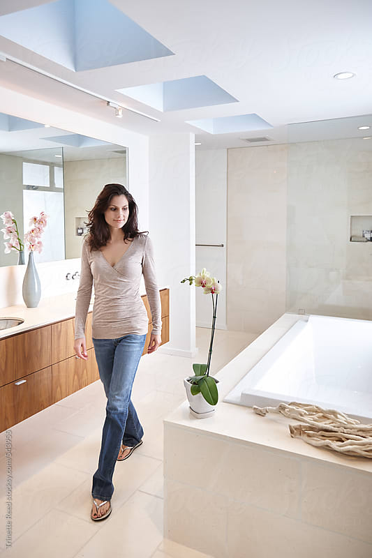 Woman walking in modern design bathroom.  by Trinette Reed for Stocksy United