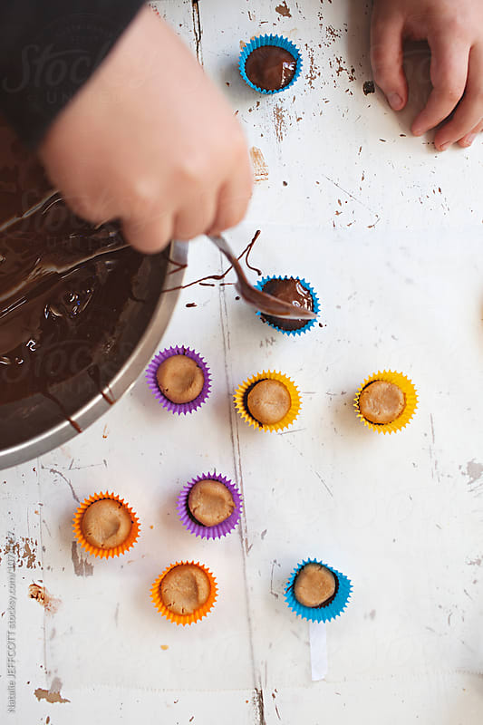Making peanut butter cups with a child by Natalie JEFFCOTT for Stocksy United