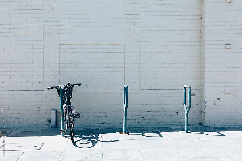 Bicycle leaning against a bike post by Jacqui Miller for Stocksy United