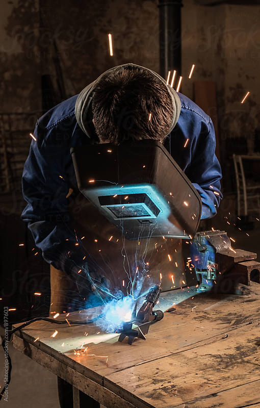 Worker working/welding metal material in small workshop. by Audrey Shtecinjo for Stocksy United