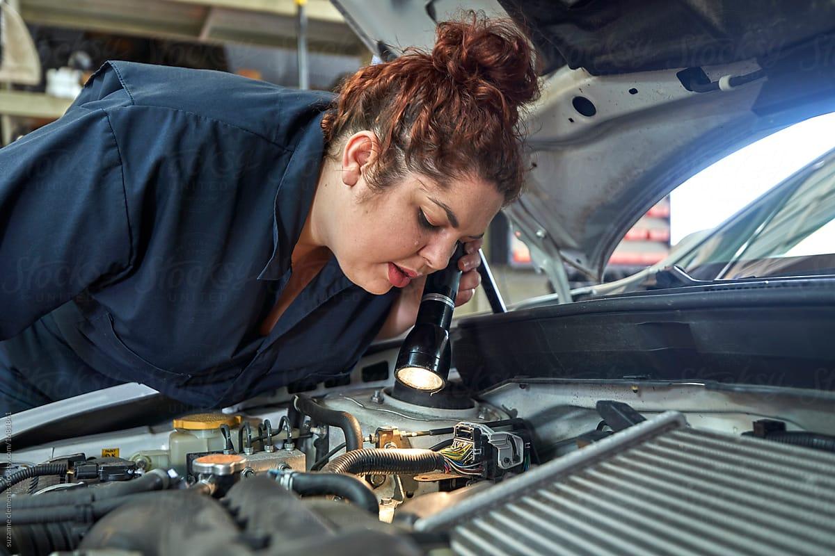 Mujer con cuerpo no normativo  arreglando el motor de un vehículo