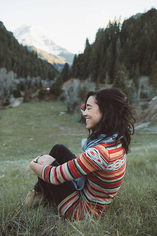 Woman Laughs with Mountains in the Background by Jake Elko for Stocksy United