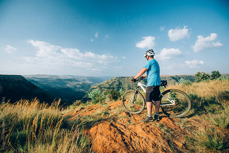 Mountain biker at the summit of a scenic mountain trail enjoying the view by Micky Wiswedel for Stocksy United
