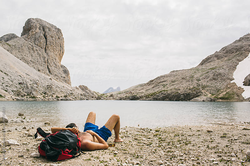 Hiker resting near a high mountain lake by michela ravasio for Stocksy United