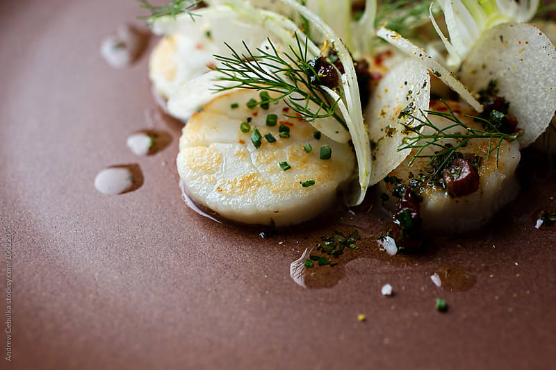 Cooked scallops with raw vegetable salad by Andrew Cebulka for Stocksy United
