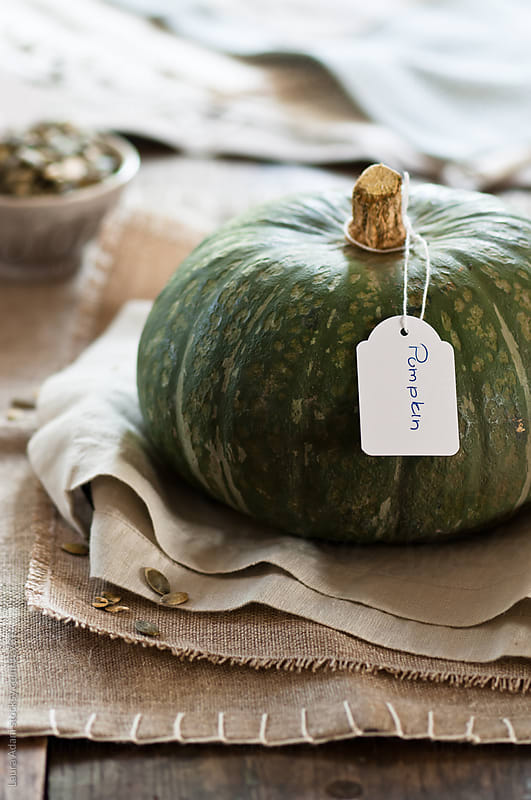 a green pumpkin and a small  bowl full of seeds   by Laura Adani for Stocksy United
