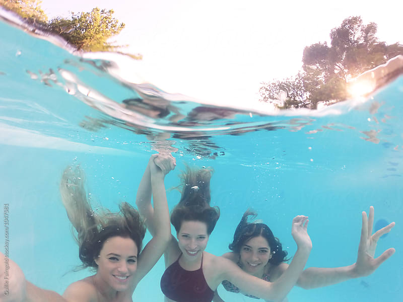 Underwater selfie of three girlfriends in pool by Guille Faingold for Stocksy United