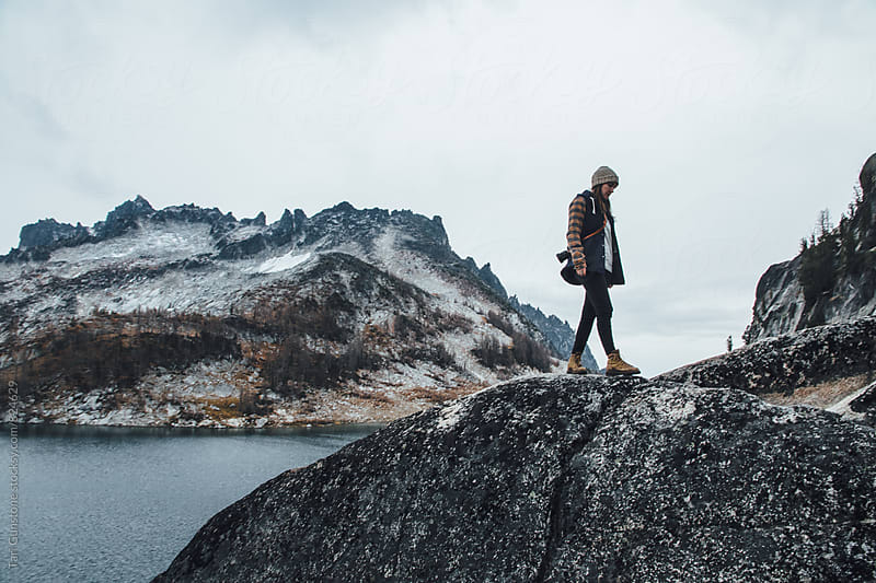 Woman walks along granite ridge above lake by Tari Gunstone for Stocksy United