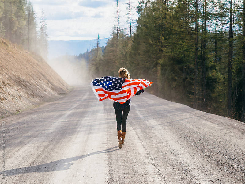 Girl running with an American Flag down a dirt road by Jeremy Pawlowski for Stocksy United
