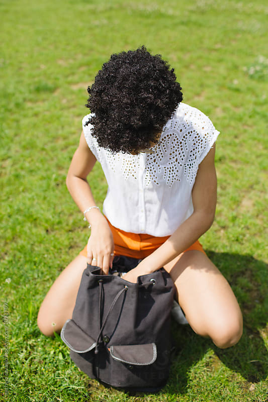 Girl rummages in her backpack by michela ravasio for Stocksy United