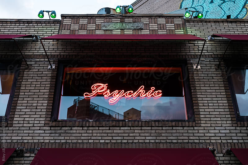 A neon sign in a window that says 'Psychic' by Riley J.B. for Stocksy United