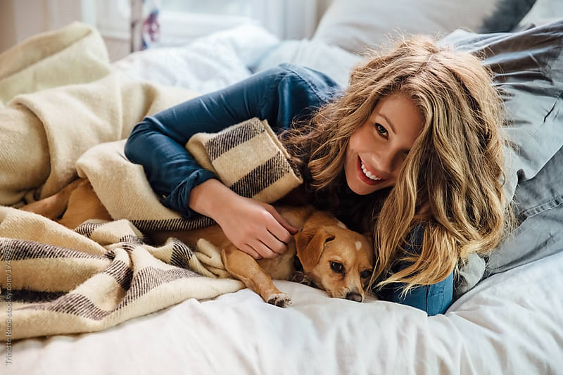 Woman relaxing with her dog by Trinette Reed for Stocksy United