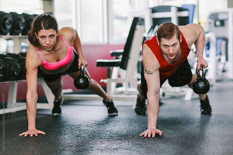 Couple working out together doing pushup row with kettlebell  in the gym by Suprijono Suharjoto for Stocksy United