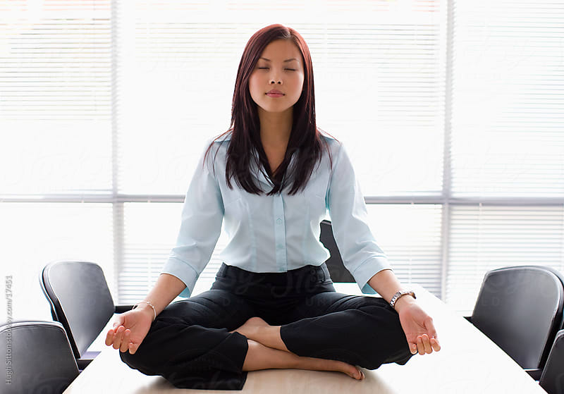 Businesswoman meditating in office. by Hugh Sitton for Stocksy United