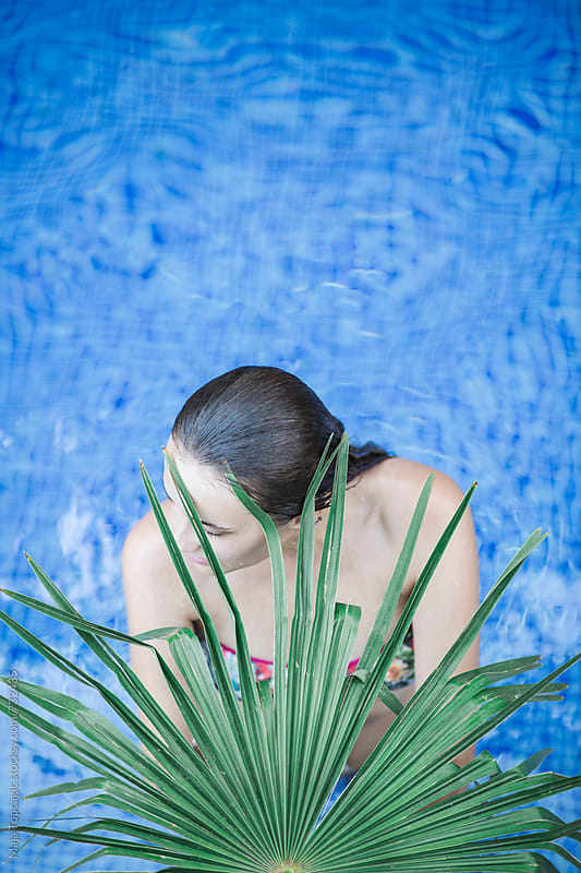 Young woman behind the palm leaves in the pool by Maja Topcagic for Stocksy United