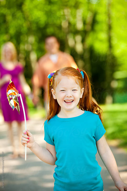 Park: Laughing Girl Walks with Pinwheel by Sean Locke for Stocksy United