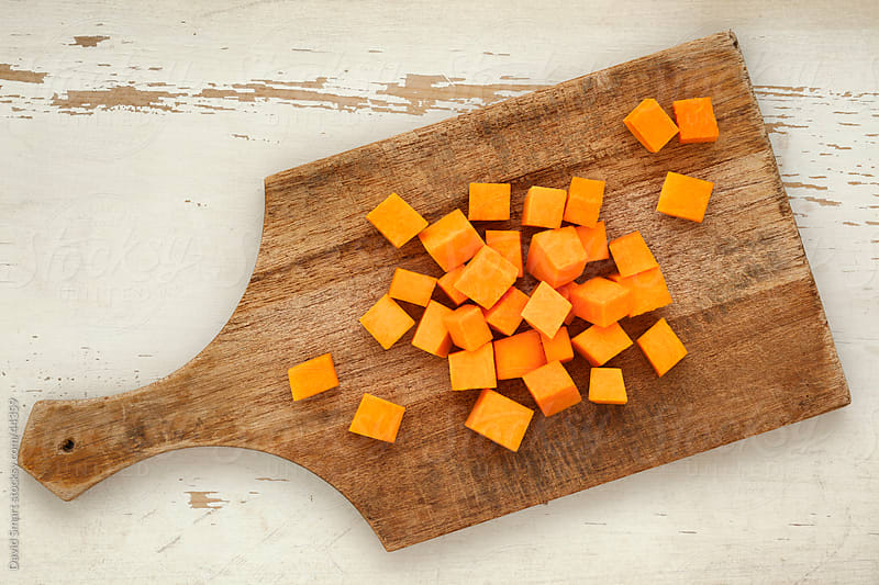 Butternut squash cubes on an old cutting board by David Smart for Stocksy United