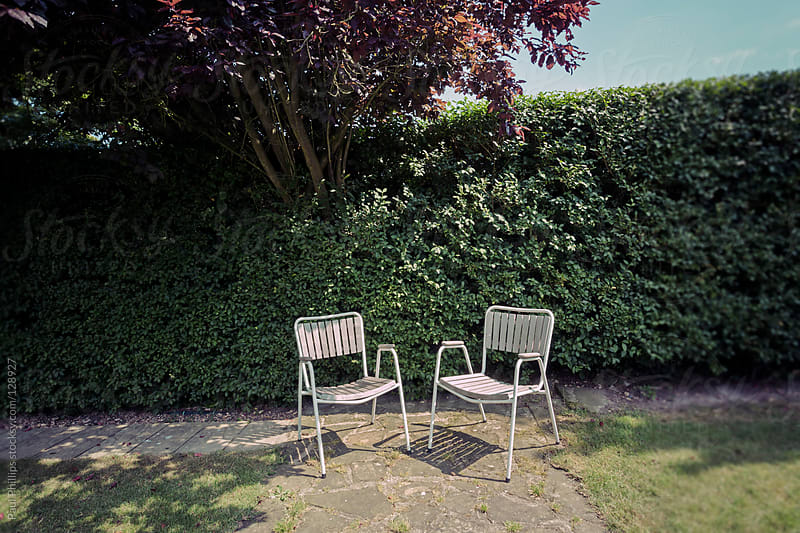 Two garden chairs on a patio area by a hedge by Paul Phillips for Stocksy United