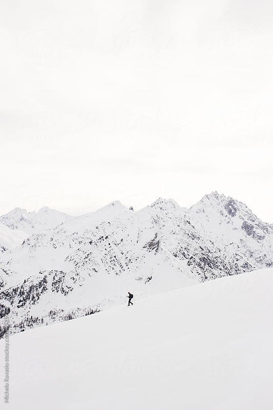 Hiker getting down the snowy mountains by michela ravasio for Stocksy United