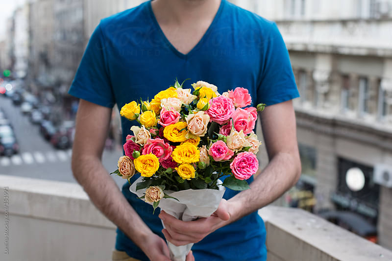 Man Holding Flowers by Lumina for Stocksy United
