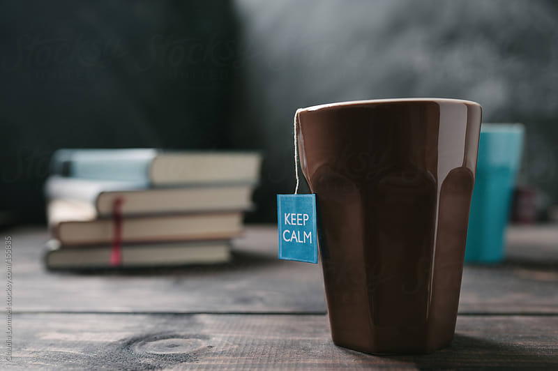 Mug, Tea Tag saying 'Keep Calm'  and a Stack of  Books on a Wooden Table by Claudia Lommel for Stocksy United