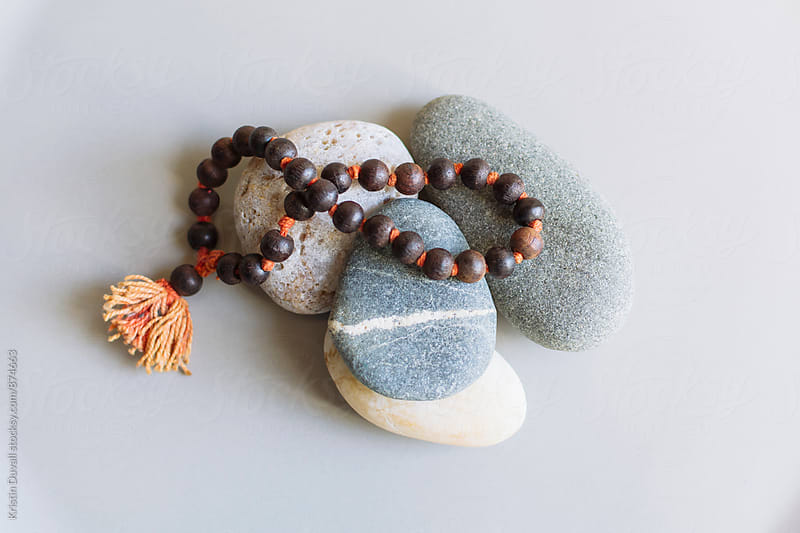 Mala beads with monochromatic stones on gray background by Kristin Duvall for Stocksy United